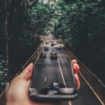This is an image of a road as seen through a smartphone being held in a hand. It is somewhat artistic.