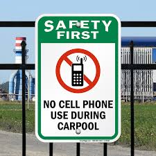 "Traffic signsays ""safety first"". co Cell phone use during  carpool. What evern parent wants to post."