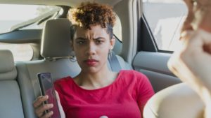 This is a passenger in a vehicle holding a smartphone. She looks angry.