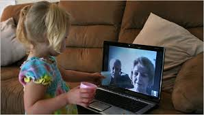 Photo of a cute little girl on a computer  screen interacting with her Grandparents. From a longer NYT article.