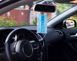 Photo of a car dashboard showing the steering wheel and a face mask dangling from the rear view mirror