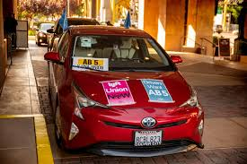 This is a California registered Prius sporting a lot of stickers supporting AB5 for Uber and Lyft drivers.