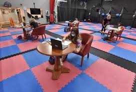Young children studying in a pod  like classroom during Covid virus. At each desk there is  computer and desks are 6' apart.
