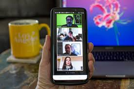 A hand holds up a phone and on their phone is a Zoom meeting with four pictures of people. There is also a yellow coffee cup in the picture.
