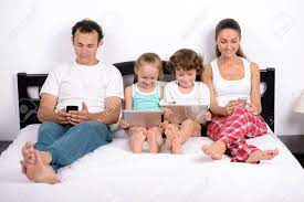 Members of a family lying in bed, each one with an electronic device.