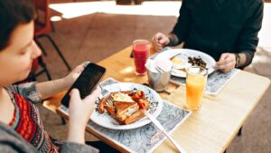 Food, Phone and Etiquette. A diner pulls out their phone while eating a meal.