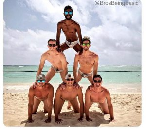 A photo of five boys forming a human pyramid. Photo taken at the beach. They are in swimsuits.